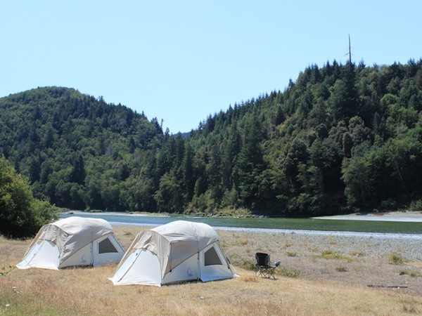 Guest tents with the river in the background